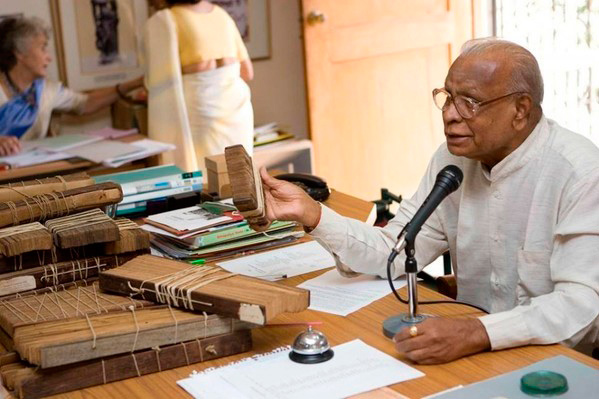 Dr V. Ganapati Sthapati estudando escritos gravados em folhas de palmeira
